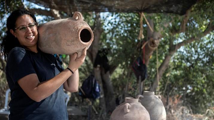 Liat Nadav-Ziv, salah satu direktur Otoritas Barang Antik Israel membawa Jar Gaza saat menemukan sisa-sisa kilang anggur Bizantium berusia 1500 tahun di Yavne, Israel (11/10/2021). (REUTERS/Nir Elias)