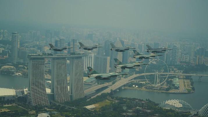 Pesawat F-16 Angkatan Udara Republik Singapura (RSAF) dan Angkatan Udara Indonesia (TNI AU) terbang dalam formasi di atas Marina Bay Sands di Singapura. (Tangapan Layar via mindef.gov.sg)