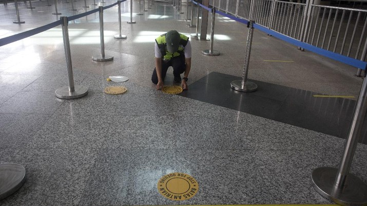 An airport worker marks queue line for the reopening of International Ngurah Rai Airport in Bali, Indonesia, Thursday, Oct. 14, 2021. The Indonesian resort island of Bali welcomed international travelers to its shops and white-sand beaches for the first time in more than a year Thursday - if they're vaccinated, test negative, hail from certain countries, quarantine and heed restrictions in public. (AP Photo/Firdia Lisnawati)