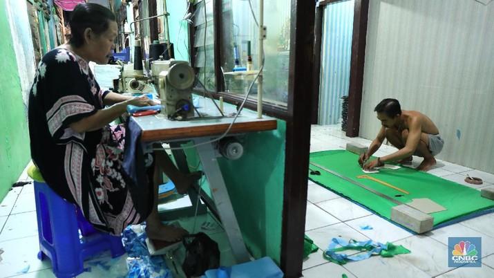 Pekerja menyelesaikan pembuatan baju wisuda (toga) di  kawasan Jakarta, Kamis (14/10/2021). Soleha (67) bisnis pembuatan baju toga sudah berjalan selama 28 tahun dan pandemi ini efeknya sangat luar biasa menurutnya.
